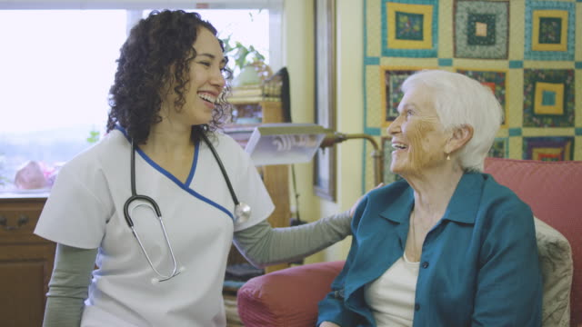 young ethnic nurse talking with elderly woman in facility - fatcamera stock videos & royalty-free footage
