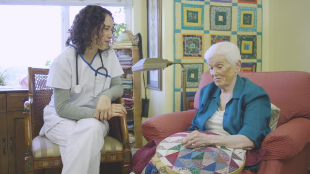 young ethnic nurse talking with elderly woman in facility while she crochets - fatcamera stock videos & royalty-free footage