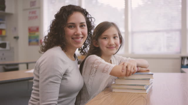 young ethnic teacher posing with her elementary school student in class - fatcamera stock videos and b-roll footage