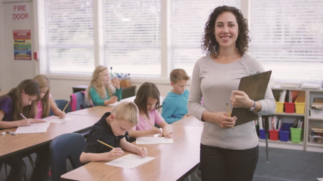 young ethnic teacher works with her elementary school students in class - elementary school stock videos and b-roll footage