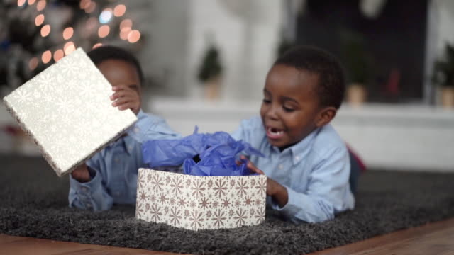 young ethnic twin brothers opening a present on christmas morning - candy cane stock videos & royalty-free footage
