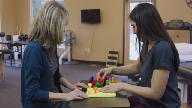 young ethnic woman at a session with a caucasian occupational therapist - rehabilitation center stock videos & royalty-free footage