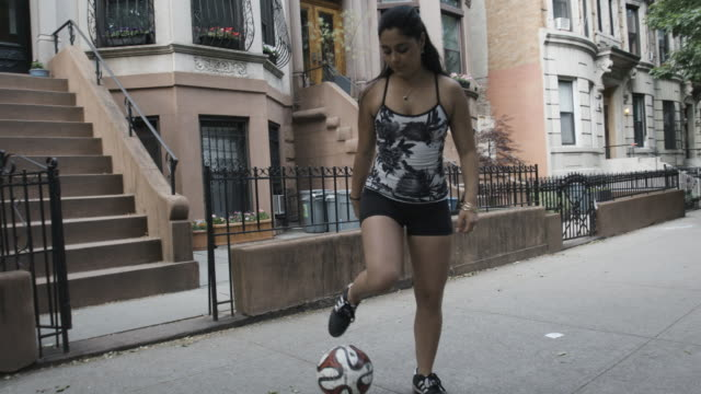 a young ethnic woman dribbles a soccer ball on a quiet brooklyn block - slow motion - 4k - lebanese ethnicity stock videos and b-roll footage