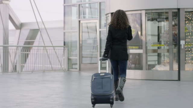 Young Ethnic Woman Entering Airport With Suitcase