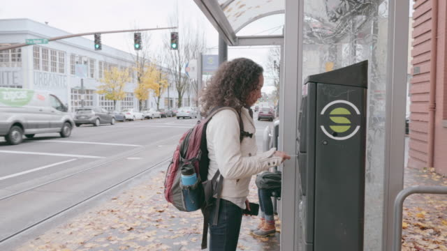 young ethnic woman paying for streetcar ticket - bus stop stock videos & royalty-free footage