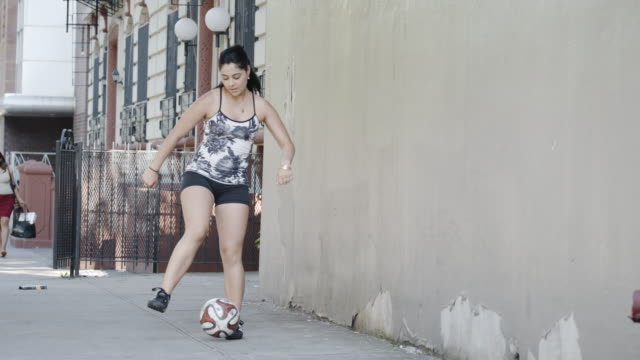 a young, ethnic woman plays soccer in the streets of brooklyn - slow motion - 4k - lebanese ethnicity stock videos and b-roll footage