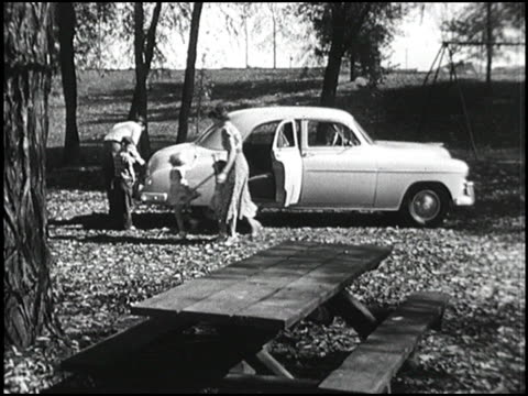 vidéos et rushes de a young family arrives at the park in their new 1949 chevrolet while mom and dad set up the food on the picnic table the young kids run around in... - chevrolet