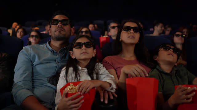 Young family at the movie theatre watching a scary 3D movie while enjoying snacks