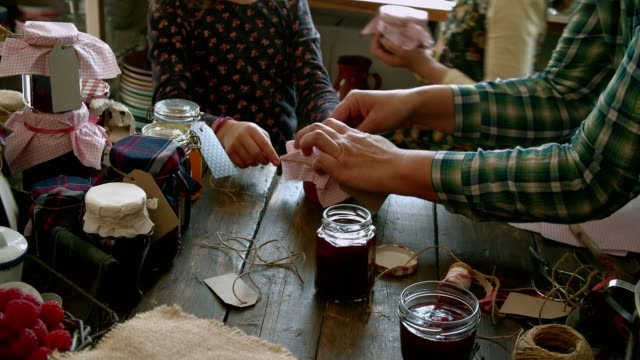 young family canning various homemade jams in jars - canning stock videos & royalty-free footage