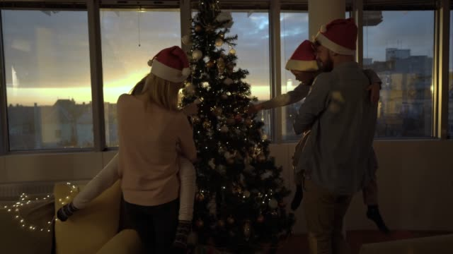 Young family decorating Christmas tree at home.