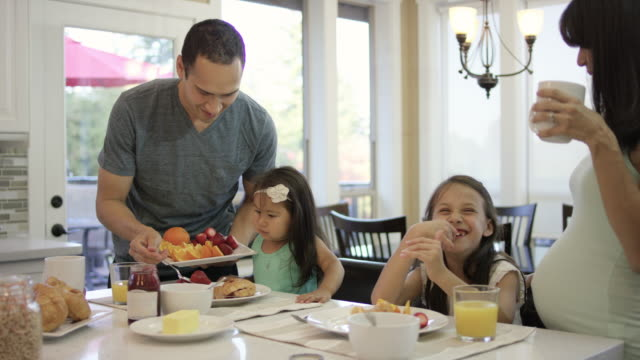 young family eating breakfast together in the kitchen - young family stock videos & royalty-free footage