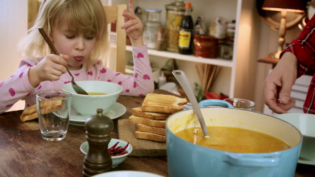 Young Family Eating Chicken Soup with Carrots and Parsnips