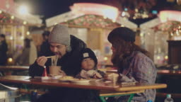 Young family enjoying street food at Christmas market at night in winter