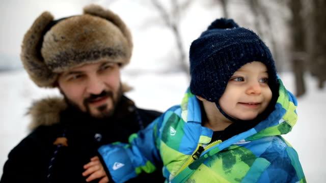 若い家族は犬と一緒に冬を楽しんでいます。父と息子 - winter点の映像素材/bロール