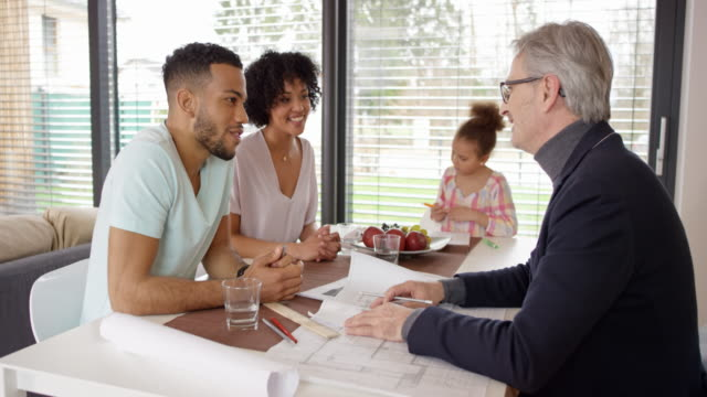 young family having a meeting with a male architect in their house - casacca video stock e b–roll