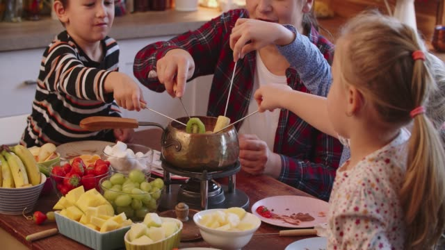 Young Family Having Delicious Chocolate Fondue in a Pot Served with Fruits
