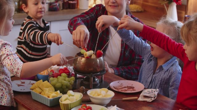 young family having delicious chocolate fondue in a pot served with fruits - fondue stock videos & royalty-free footage