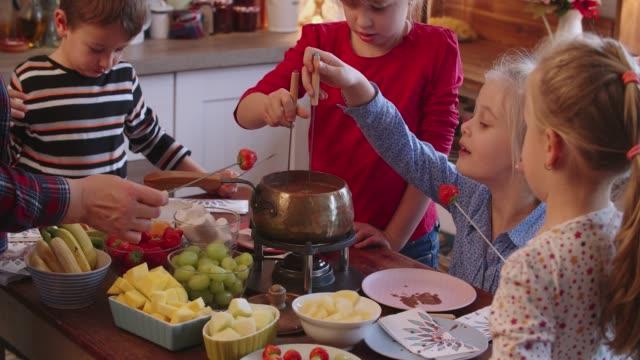 vídeos y material grabado en eventos de stock de familia joven con delicioso fondue de chocolate en una olla con frutas - mojar