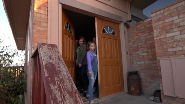 正面玄関から向かって若い家族 - 建物入口点の映像素材/bロール