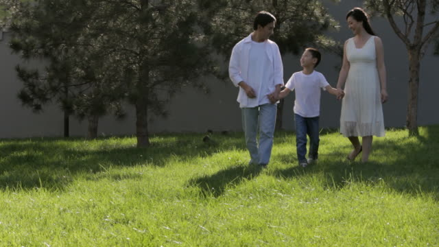 ms young family holding hands walking through park / china - familie mit einem kind stock-videos und b-roll-filmmaterial
