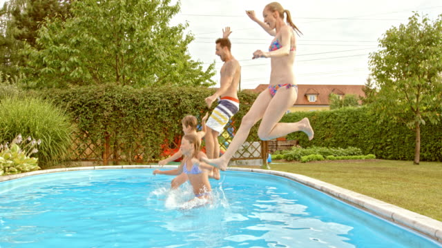 SLO MO TS Young family jumping into the pool together