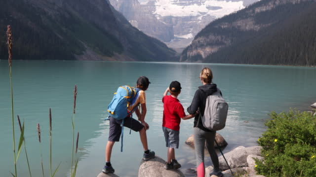 young family look out across lake louise, on hike - national park stock videos & royalty-free footage