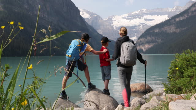 young family look out across lake louise, on hike - t shirt stock videos & royalty-free footage
