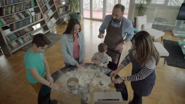 vídeos de stock, filmes e b-roll de família jovem fazer massa em casa - massa alimento básico