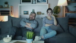 Young family man and woman watching boring movie on TV at home at night yawning
