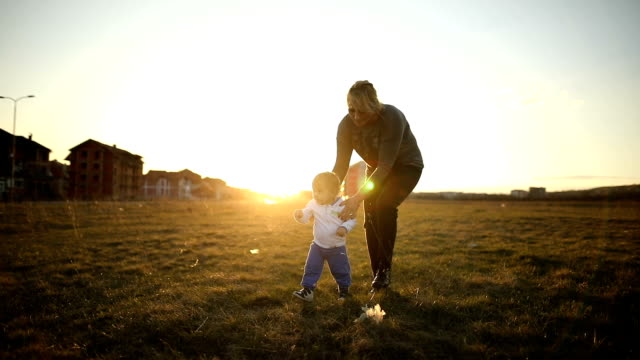 young family, mother and son walking together at sunset. - one parent stock videos & royalty-free footage