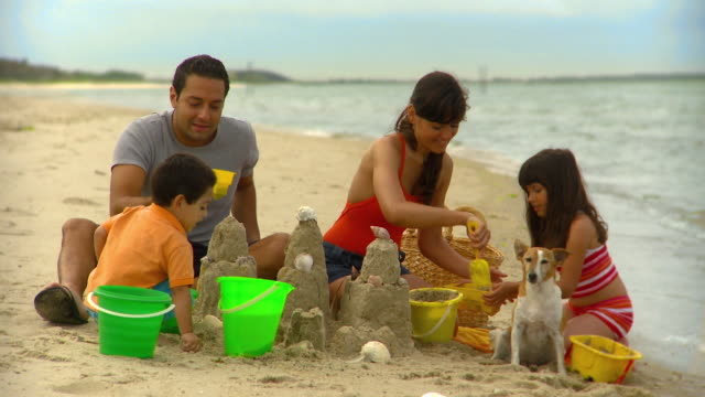 MS Young family of four building sand castles on beach, Eastville, Virginia, USA