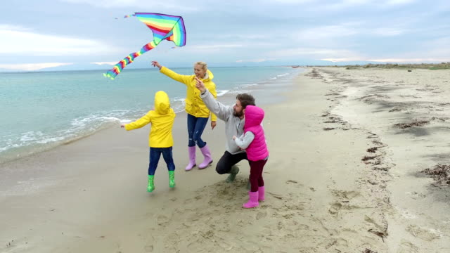 young family on the beach - kite toy stock videos and b-roll footage