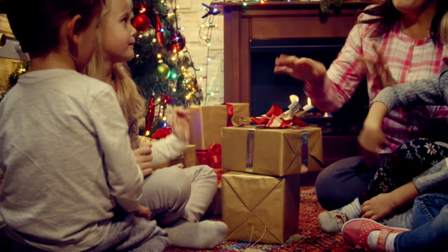 Young Family Opening Christmas Presents