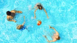 A young family playing ball in the pool on a sunny day