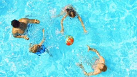 famiglia giocando con la palla in piscina - swimming pool video stock e b–roll