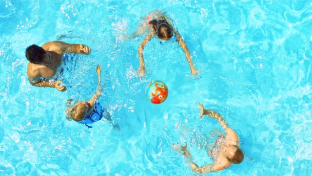 a young family playing ball in the pool on a sunny day - swimming pool stock videos & royalty-free footage