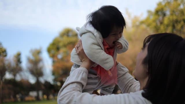 一緒に公園で遊ぶ若い家族 - ピクニック点の映像素材/bロール