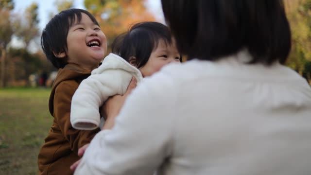 一緒に公園で遊ぶ若い家族 - public park点の映像素材/bロール