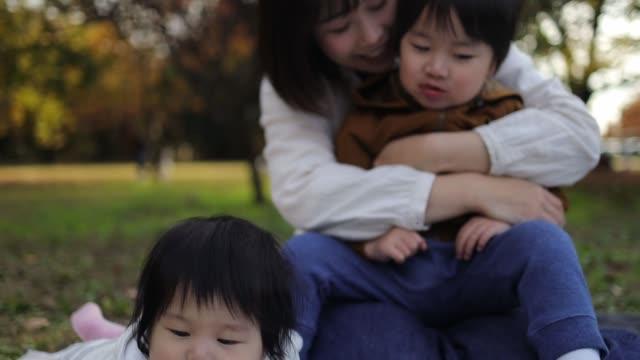一緒に公園で遊ぶ若い家族 - 子供2人の家庭点の映像素材/bロール