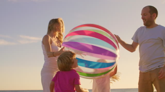 Young family playing with beach ball on beach