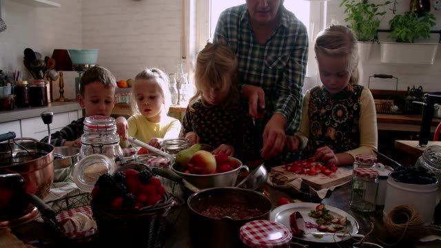 Young Family Preparing Homemade Berry Jam and Canning in Jars