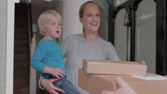 vidéos et rushes de young family receiving a home delivery - facteur