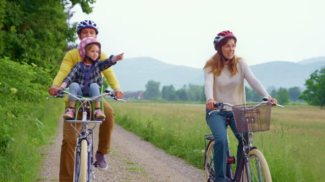 slo mo ts young family riding bikes in nature and small daughter sitting in child bike seat - bicycle seat stock videos & royalty-free footage