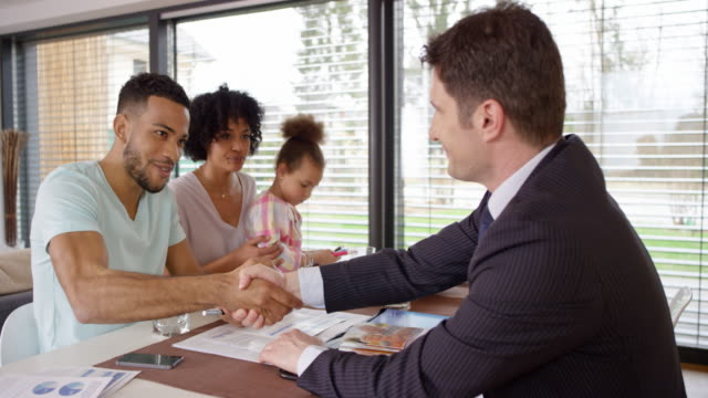 Young family shaking hands with personal banker at their home