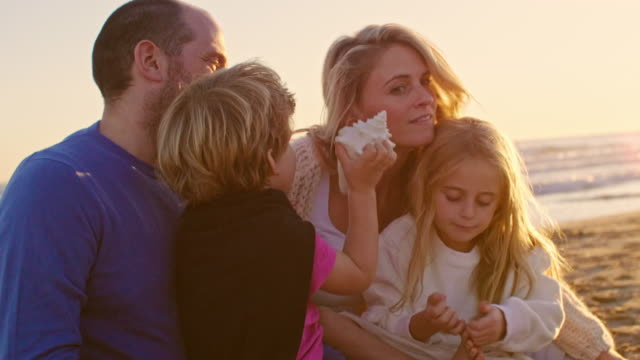 young family sitting together on beach playing with sea shell - seashell stock videos & royalty-free footage