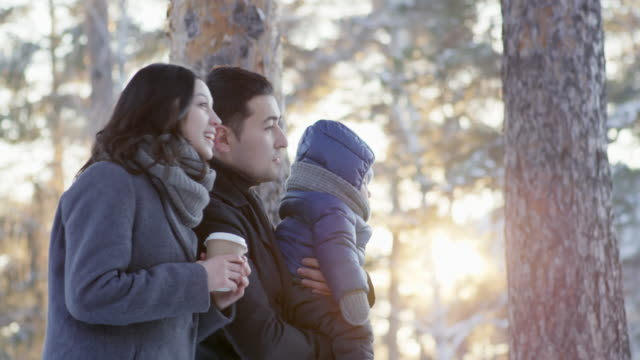 Young family standing in the park with baby at sunny winter day