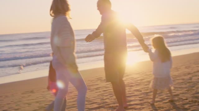Young family walking and playing on beach in sunset