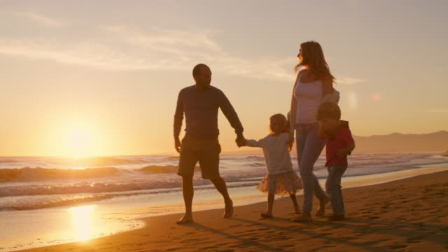 Young family walking and playing on beach with children holding hands in sunset