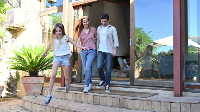 young family walking from home interior to outdoor courtyard - courtyard stock videos & royalty-free footage