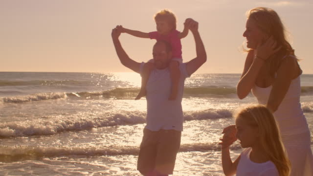 Young family walking on beach in sunset